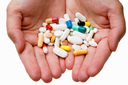 Opened hands offering assorted multicolored pills and capsules. Close up.