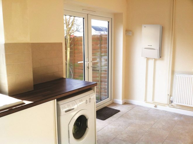 Photo showing a modern kitchen diner room in a domestic house, with white glossy cabinets, an upright automatic washing machine, a ceramic sink located in front of a window, beige wall tiles and a brown tiled floor. The floor tiles have a mottled pattern, which helps to disguise a dirty floor. Double glazed patio doors / French windows lead into the back garden, where there is a lawn, wooden larch-lap fence panels, various flower pots and plants, and a wood picnic table. A doormat can be seen by the concrete paving slabs.
