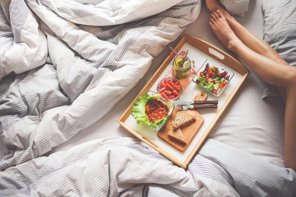 ženske noge in pladenj z zdravo hrano na postelji