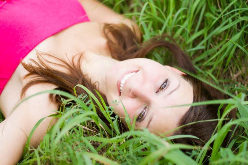 ženska leži sproščena in zadovoljna v travi