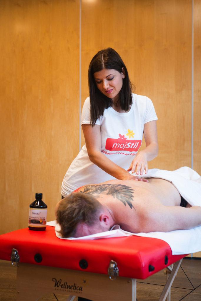Ženska masira moškega na rdeči masažni mizi