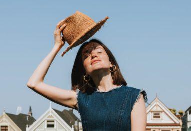 ženska s klobukom na soncu
