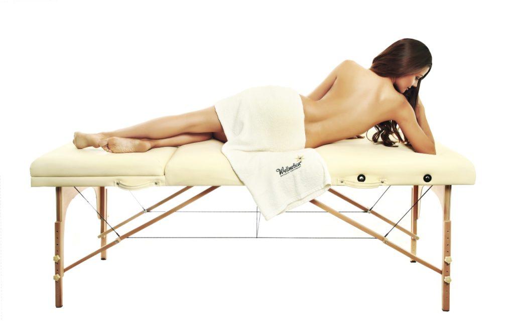 ženska z dolgimi lasmi, pokrita z brisačo leži gola na masažni mizi