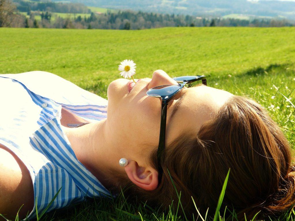 ženska s sončnimi očali leži na travniku z marjetico v ustih