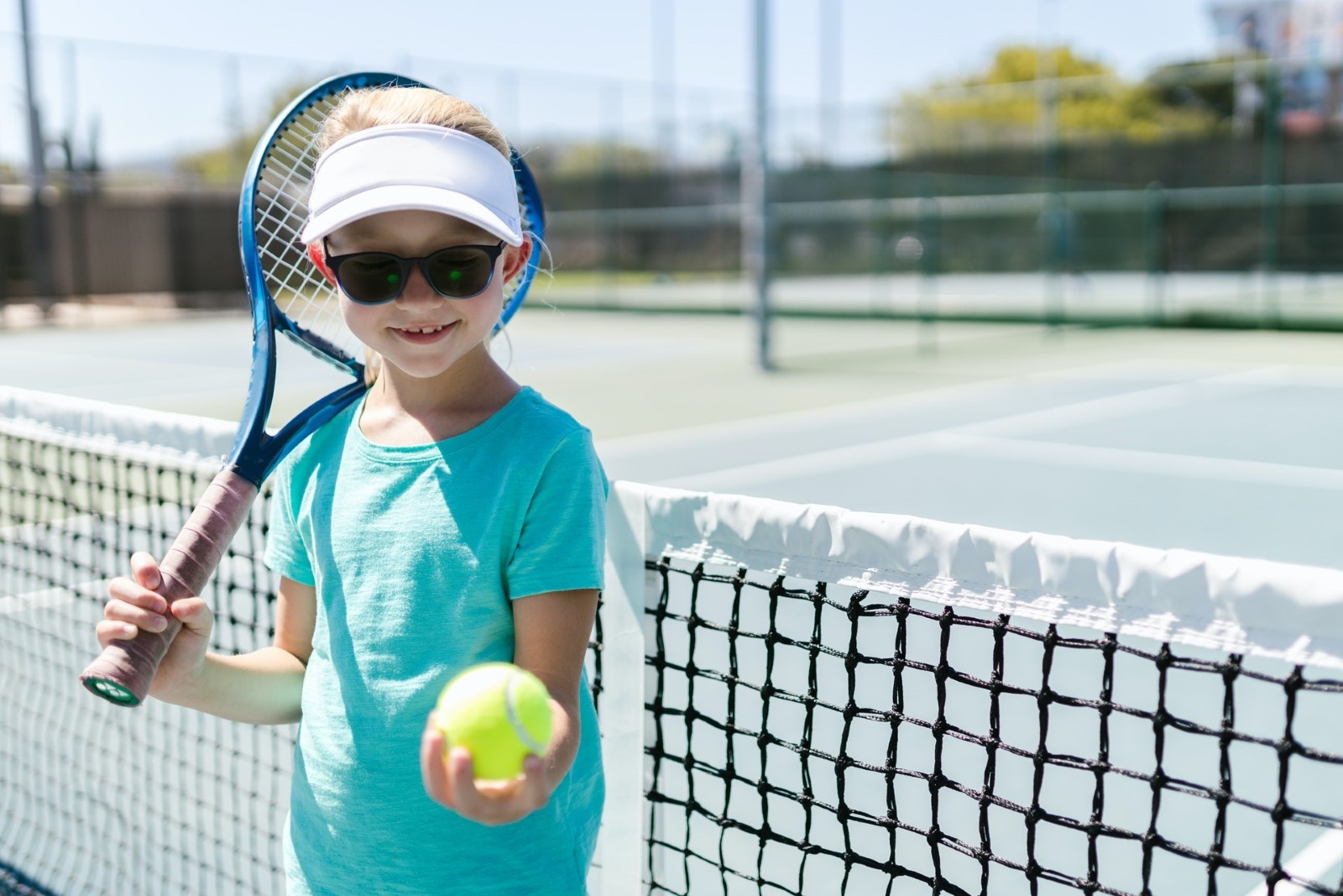 A child holding a tennis racket  Description automatically generated with medium confidence